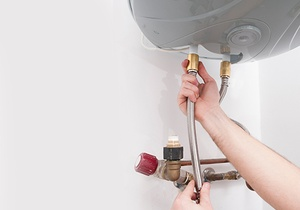 Hands repairing the plumbing pipes of an electric boiler.